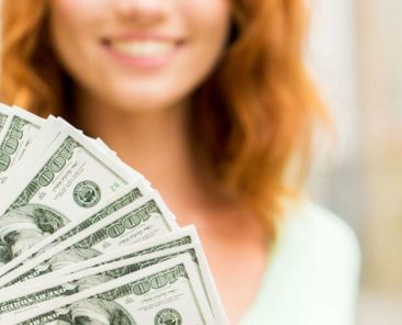 smiling woman and hundred dollar bills